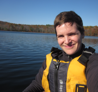 Mary in a life jacket with a lake in the background