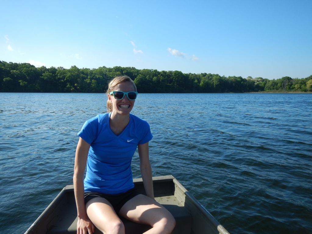 person smiling at the camera sitting in a small boat on a lake