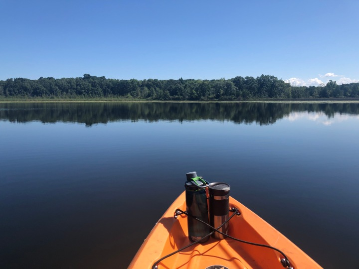 front end of a kayak with a water bottle and coffee mug visible, with a calm lake in front and trees in the distance
